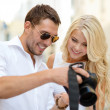 Smiling couple with photo camera — Stockfoto