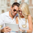 Couple looking at tablet pc in cafe — Stock Photo #37246293