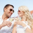 Smiling couple in sunglasses drinking wine in cafe — Stock Photo