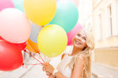 Smiling woman with colorful balloons — Stock Photo
