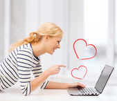 Smiling student girl pointing her finger at laptop — Stock Photo