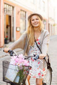 Attractive woman in hat with bicycle in the city — Stock fotografie