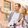 Couple with bicycles taking photo with camera — Stock Photo