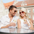 Smiling couple in sunglasses drinking wine in cafe — Stock Photo #37406249