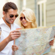 Smiling couple in sunglasses with map in the city — Stock Photo #37406469