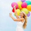 Smiling woman with colorful balloons outside — Stockfoto