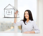 Smiling woman drawing house on virtual screen — Stock Photo