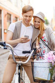 Couple with smartphone and bicycles in the city — Stock Photo