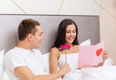 Smiling couple in bed with postcard and flower — Stock Photo