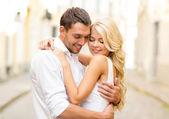 Romantic happy couple hugging in the street — Stock Photo