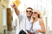Couple with map, camera and travellers guide — Stock Photo