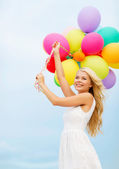 Smiling woman with colorful balloons outside — Stock Photo
