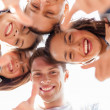 Stock Photo: Group of smiling teenagers looking down