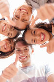 Group of smiling teenagers looking down — Stock Photo