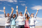 Group of smiling teenagers holding hands up — Stock Photo