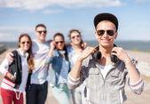 Güneş gözlüğü ve arkadaşlarıyla dışarıda genç çocuk — Stok fotoğraf