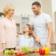 Happy family making dinner in kitchen — Stock Photo #37461187