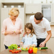 Happy family making dinner in kitchen — Stock Photo #37461359