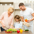 Happy family making dinner in kitchen — Stock Photo #37461365