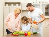 Happy family making dinner in kitchen — Stockfoto
