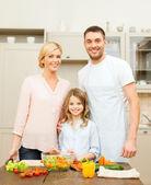 Happy family making dinner in kitchen — Zdjęcie stockowe