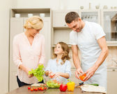 Happy family making dinner in kitchen — Stock Photo