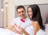 ポストカードとの花のベッドでカップルの笑みを浮かべてください。 — ストック写真