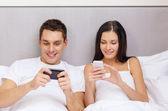 Casal sorridente na cama com smartphones — Fotografia Stock