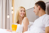 Smiling couple having breakfast in bed in hotel — 图库照片