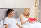 Smiling couple in bed with red gift box — Stock Photo