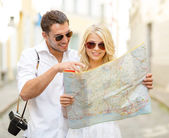 Smiling couple in sunglasses with map in the city — Stock Photo