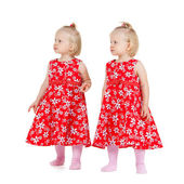 Two identical twin girls in red dresses looking — Stockfoto