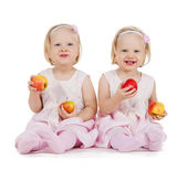 Two identical twin girls playing with apples — Stock Photo