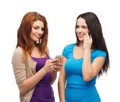 Dva teenageři usmívající se smartphony — Stock fotografie