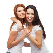 Two laughing girls in white t-shirts hugging — Stock Photo