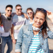 Teenage girl with headphones and friends outside — Stock Photo #37591263