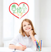 Smiling little student girl drawing at school — Stock Photo
