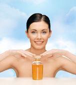 Beautiful woman with oil bottle — Stockfoto