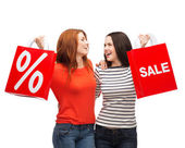 Two smiling teenage girl with shopping bags — Stock Photo