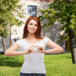 Smiling girl showing heart with hands — Stock Photo #38312069