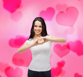 Smiling girl showing heart with hands — Stock Photo