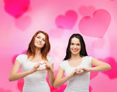 Two smiling girls showing heart with hands — Stock Photo
