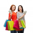 Smiling teenage girls with shopping bags and money — Stock Photo