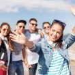 Teenage girl with headphones and friends outside — Stockfoto
