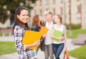 Teenage girl with folders and mates on the back — Stock Photo