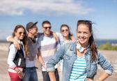 Tonårsflicka med hörlurar och vänner utanför — Stockfoto