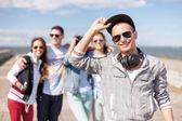 Tonårspojke med solglasögon och vänner utanför — Stockfoto