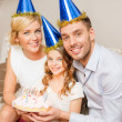 Smiling family in blue hats with cake — Stock Photo #38360987