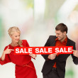 Woman and man pointing finger to red sale sign — Stock Photo