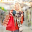 Smiling teenage girl with shopping bags — Stock Photo #38429279